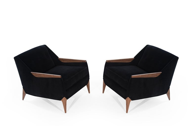 Stunning pair of sculptural Italian lounges chairs. Fully restored to their original integrity. They boast hand-cut high-grade foam. They have been recovered in deep blue Mohair by Beacon Hill. Walnut arms and legs fully restored.