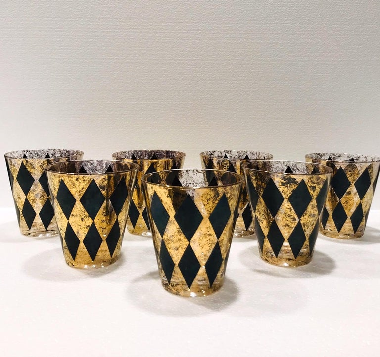 Set of seven Mid-Century Modern rock glasses with Harlequin design. Whiskey cocktail set features large hand blown glass with tapered design with 22-karat gold leaf flecks and black diamond patterns throughout. Hollywood Regency set makes a chic
