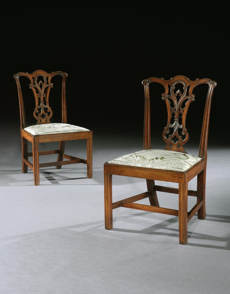 A very fine set of George III mahogany side chairs in the manner of Thomas Chippendale. Each chair with an elaborate finely carved interlaced back splat above a drop-in seat with upholstered cushion, standing on square chamfered legs joined by an