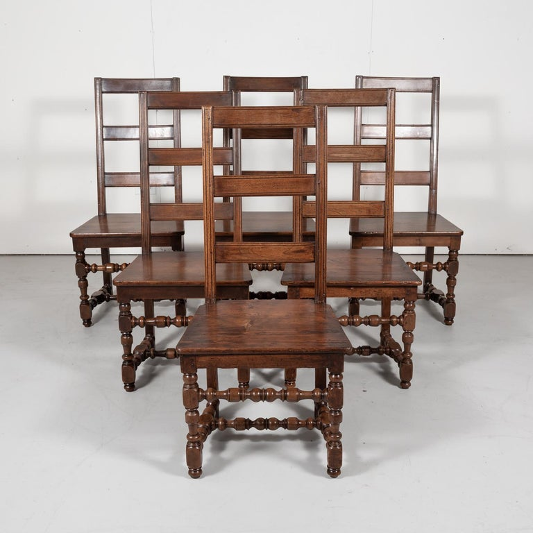 Hard to find set of six French Louis XIV style ladder back dining chairs in walnut, each having a squared back with three horizontal slats and solid wood seat, circa 1890s. Raised on turned front legs and squared back legs with an H-stretcher and