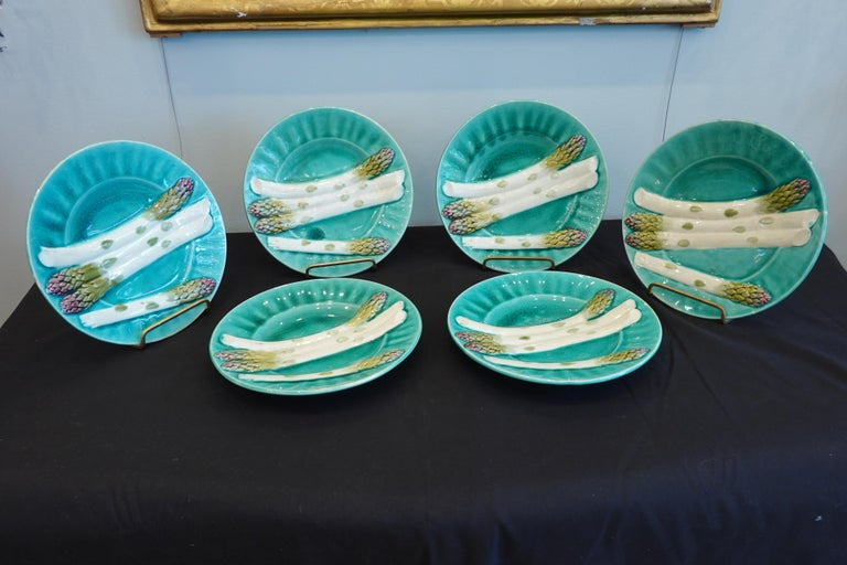 Set of very decorative, late 19th century blue-green French Majolica asparagus plates, hand-painted in white, green and purple, showing four asparagus spears in relief, and with fluted rims. The underside is stamped