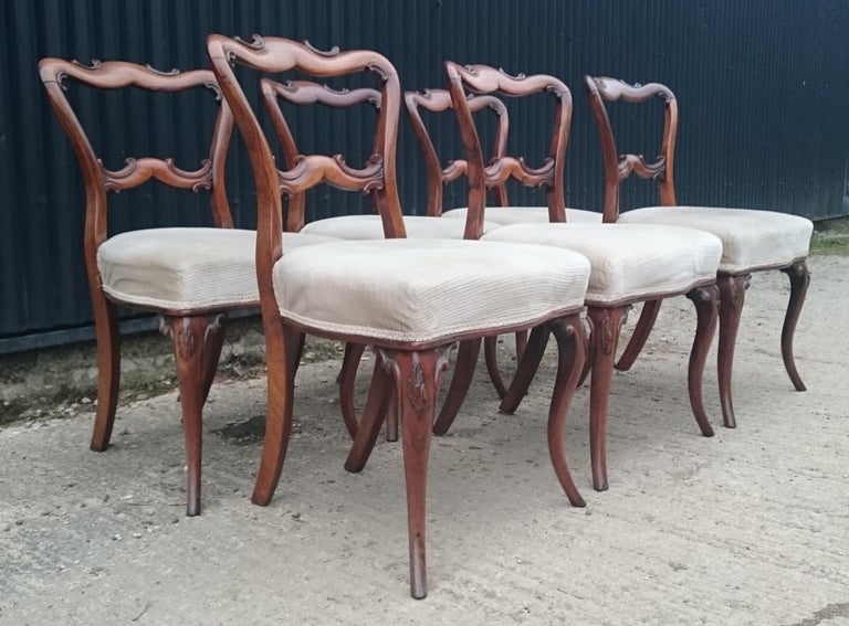 Set of six antique dining chairs standing on elegant cabriole legs. These chairs have the earlier type of corner stretchers which would indicate that they are an early version of this design. This is a very Fine quality set of chairs and the