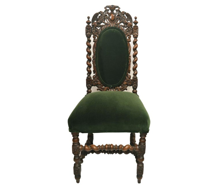 This gorgeous set of six antique hand carved oak chairs has magnificent carving with two griffins framing a crest at the top of the chairs and the sides of the chairs accented in barley twist frames. The chairs have been reupholstered in a luxurious