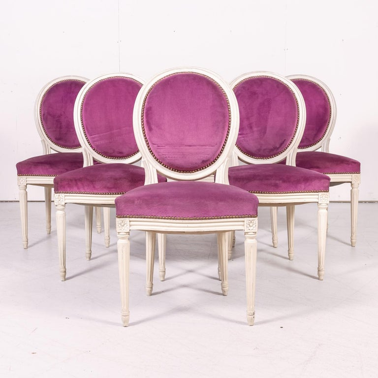 Set of six French Louis XVI style carved and painted side chairs having the original creamy white painted finish, circa 1920s. Upholstered medallion shaped backs and serpentine seats with nailhead trim, all raised on stop-fluted tapering legs headed