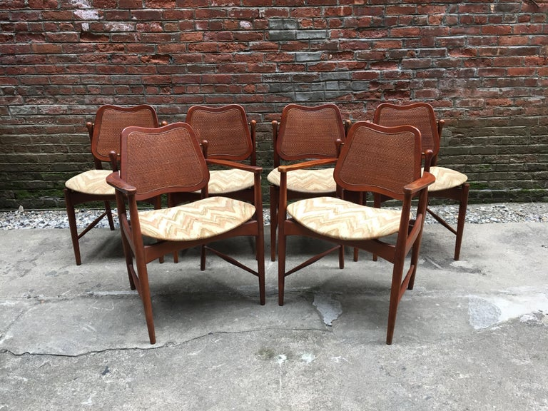 Early and good set of six Danish modern Arne Vodder designed teak and cane back chairs. These beautiful chairs feature solid teak construction, inset caned backs, and brass fittings so the back of the seat tilts when you move for constant back