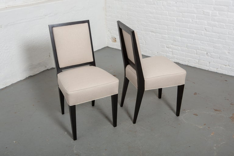 Set of 6 newly upholstered and restored French Art Deco Style ebonized chairs with off-white upholstery. Straight back and slightly tapered sculptural legs. Measures: 15.5
