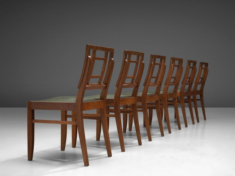 Set of six Art Deco dining chairs in solid oak, France, 1940s  This set of French dining chairs show a basic design, with strong proportions. The geometric backrest is a typical feature from the Art Deco, which also gives the chair an open