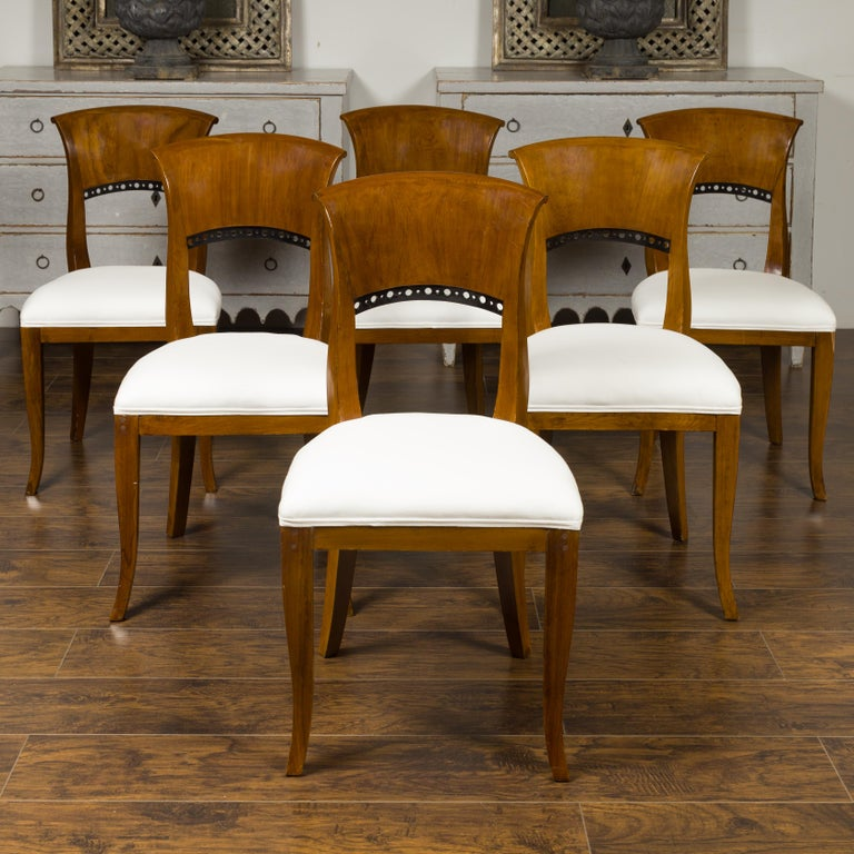 A set of six Austrian Biedermeier style walnut dining room chairs from the late 19th century, with ebonized accents and new upholstery. Born in imperial Austria during the last quarter of the 19th century, each of this set of six dining room side