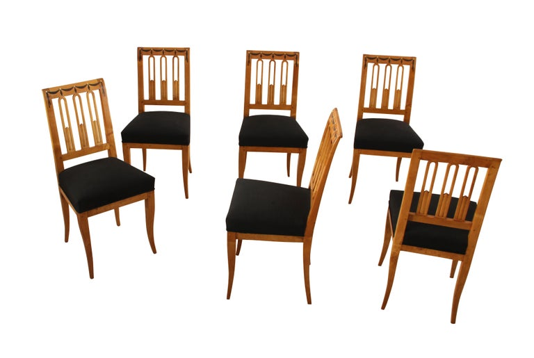 Set of six early Biedermeier chairs with a classicist influence and a Gothic influenced arc back-decor.  The chairs are made from a beautiful birch solid wood. Around the top of the chairs there is are inlay marquetries made of ebony and bone, in