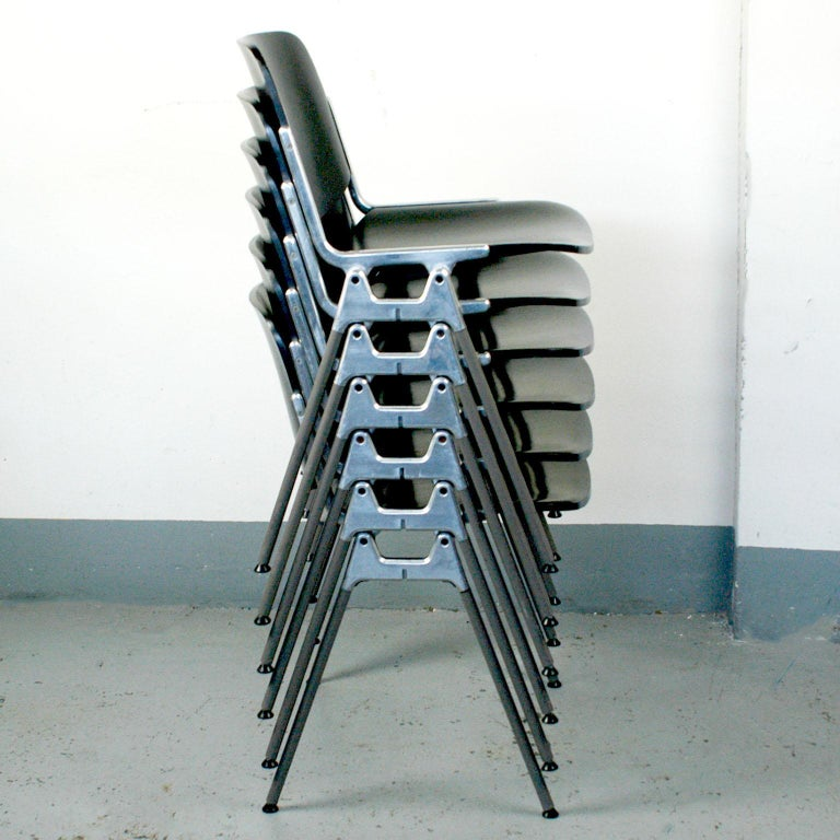 Set of six iconic DSC 106 stacking chairs, designed 1965 by Giancarlo Piretti for Castelli. This set features black lacquered seats and backs they are in very nice condition with a few signs of wear due to their age. Perfect and stylish to use as