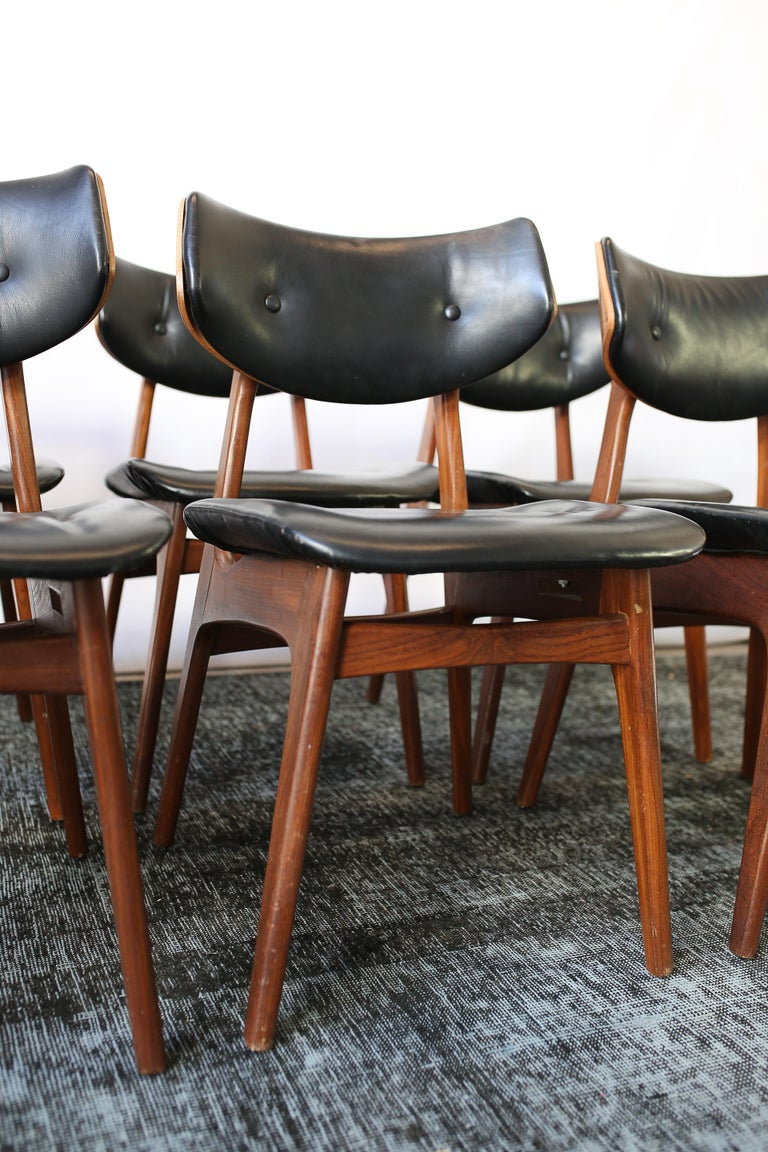 This set of six Danish modern teak and black leather dining chairs are in overall good condition and wear consistent with age and use.  circa 1960s. Denmark. Dimensions: D 18.25