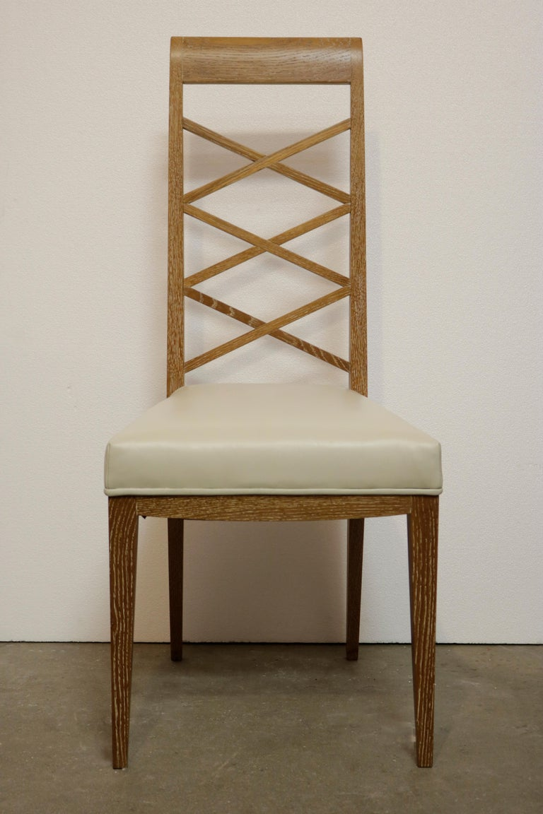 Set of six elegant dining chairs in the style of French designer Jacques Adnet. Made of cerused oak, these chairs feature an open cross back design and a seat upholstered in creamy white leather.