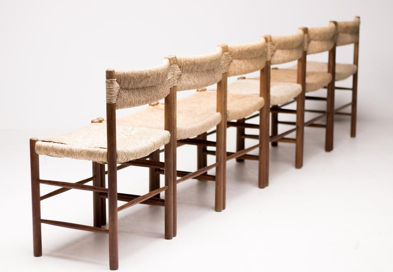 Wonderful set of 6 dining chairs model Dordogne designed by Charlotte Perriand for Sentou.  Ashwood structure with rush seat and backrest.  A Pioneer of modernism in France, Charlotte Perriand was one of the most influential figures in 20th