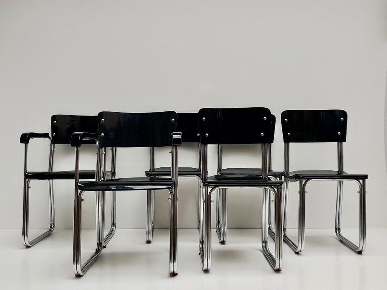 Set of six chroom Bauhaus chairs with plywood seat and backrest, 1930s The set has two armchairs and four normal chairs.  German Art Deco black enameled wood armchair with chrome trim having a shaped wood back and cane seat (design attributed: