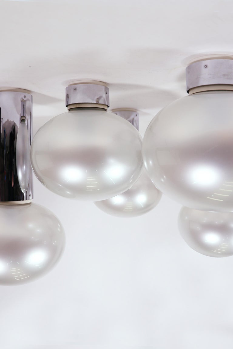 Set of six chromed steel and mother of pearl lights designed by Motoko Ishii for Staff, Germany in the 1970s. They feature large blown glass mother-of-pear globes. Measures: Height 11 in. / 28cm, 15 in. / 38 cm, 19 in. / 48 cm Diameter 9.45 in. /