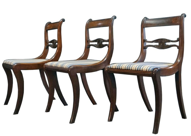 A very fine set of six federal-era saber leg dining chairs, attributable to New York cabinetmaker, Duncan Phyfe. Made of a fine and dense mahogany, these American classical chairs offer a figured mahogany veneer on the crest rail, a carved centre