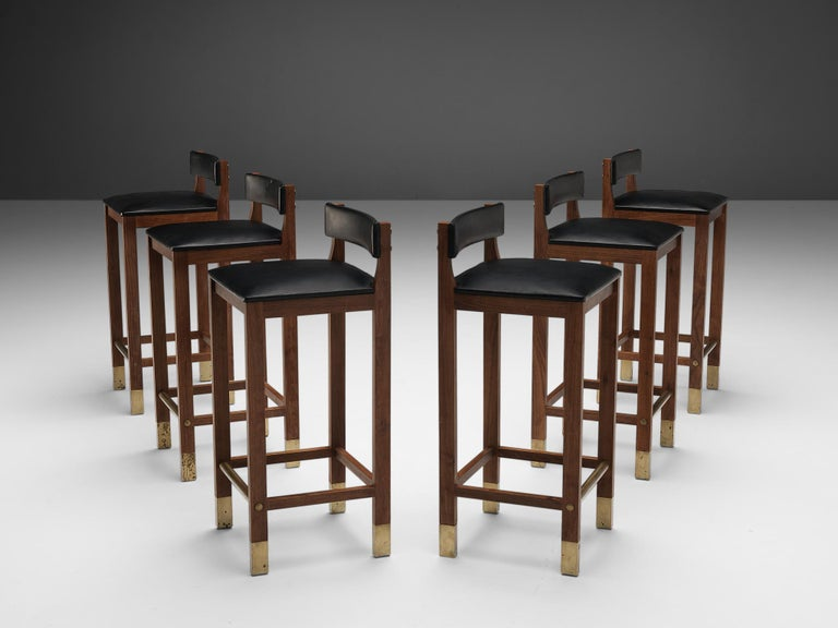 Set of six Danish bar stools, teak, brass, leatherette, Denmark, 1960s  This set of six Danish bar stools shows a strong design that features brass feet on the teak frame as well as a brass footrest and black leatherette upholstered seats. The seat