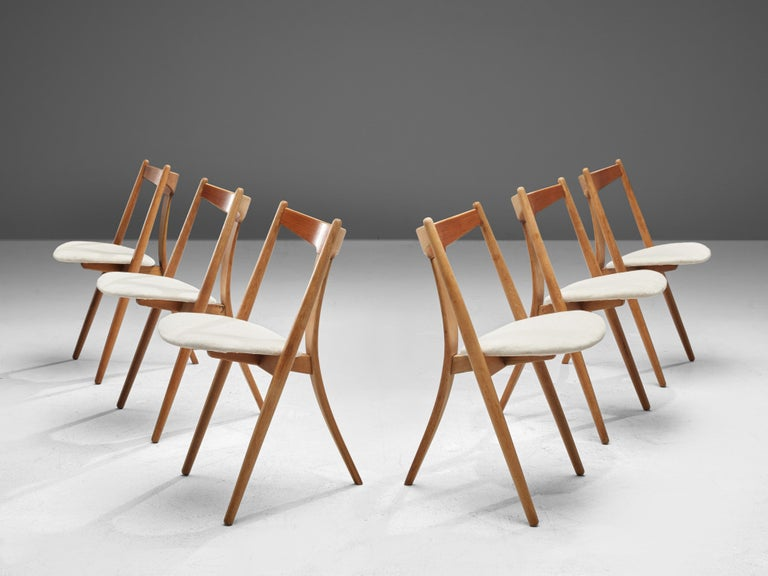 Dining chairs, teak, oak, fabric, Denmark, 1950s  This set of six chairs is made by a cabinetmaker in Denmark. The chairs have a tripod base made of oak and a backrest executed in teak. The main characteristic is the bent single back leg. The leg