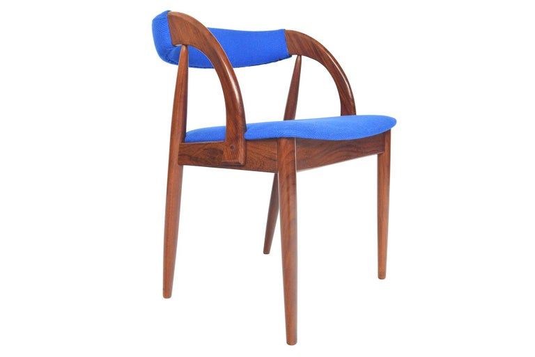 Elegant and exceedingly comfortable, this set of six Danish midcentury walnut dining chairs is the perfect companion for any modern dining room. Sculpted walnut creates a stunning profile from the side and wraps around to offer an upholstered