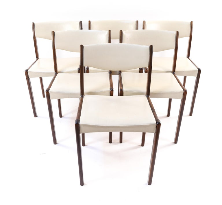 This is a wonderful set of six Danish midcentury dining or side chairs by Sax, circa 1960s. These chairs have a timeless modern design, with rosewood frames and white leather upholstery. Their sleek appearance serves them well to fit around a dining