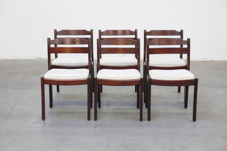 This lovely set of six (6) Danish Modern Rosewood dining chairs are by Dyrlund, circa 1960s, sculpted from Rosewood with white leatherette upholstery, these are a perfect option for interior designers and Mid-Century Modern enthusiasts. Signed
