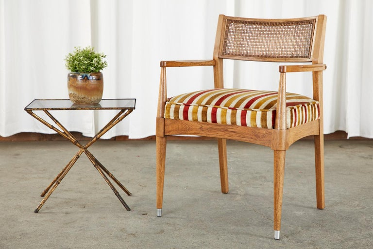 Marvelous set of mid-century dining chairs by B. P. John. Crafted from walnut in the Danish modern taste. The set consists of four side chairs and two armchairs measuring 23 inches wide. The chairs feature an original cane inset on the curved