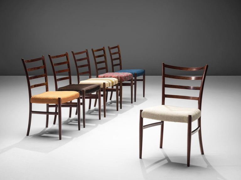 Set of six dining chairs, rosewood and varied types of fabric, Denmark, 1960s.  This set of rosewood chairs have a warm grained frame. The chairs are built up of a slatted back with four slats and a minimalist, clean frame. The organic frame