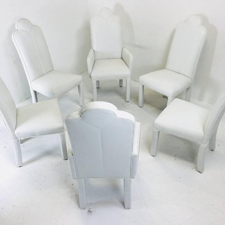 Set of six deco parson style white vinyl dining chairs. Chairs are in good vintage condition with minimal wear from use and age. New upholstery is recommended.  Set includes two Armchairs and four side chairs  Dimensions: 20