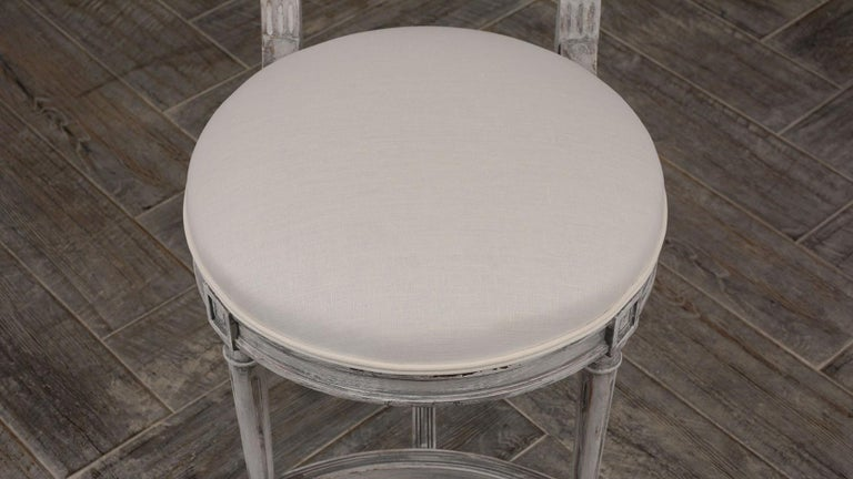 Set of six elegant painted dining chairs. Solid mahogany wood frames with carved back details, newly painted in a beautiful pale gray color with a distressed finish. Seats have been professionally reupholstered in a Belgium off white linen fabric