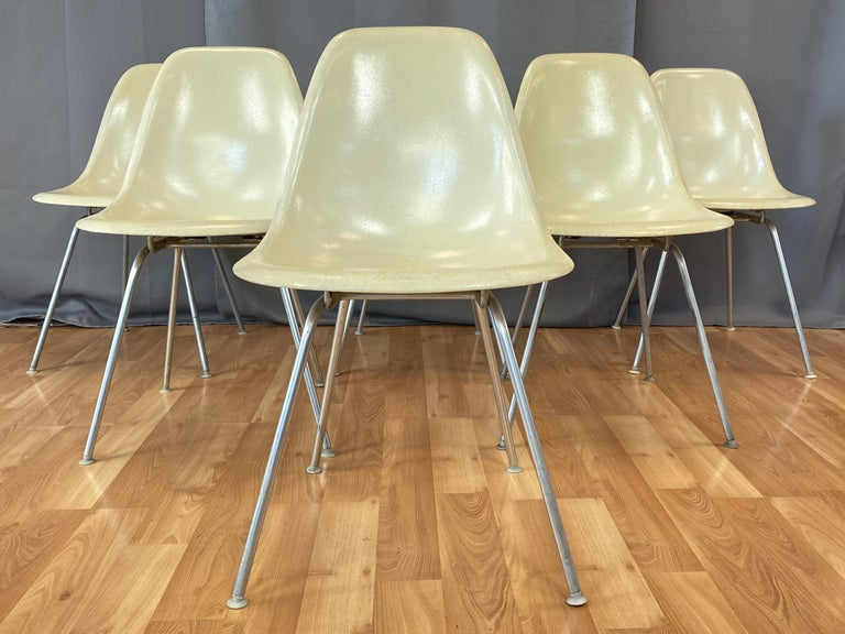 A set of six circa 1959 parchment color fiberglass side chairs with original bases by Charles and Ray Eames for Herman Miller.  Five chairs are DSX on narrow mount 'H' bases, and one chair is DSG (Dining Side Guard) on narrow mount 'H' base with