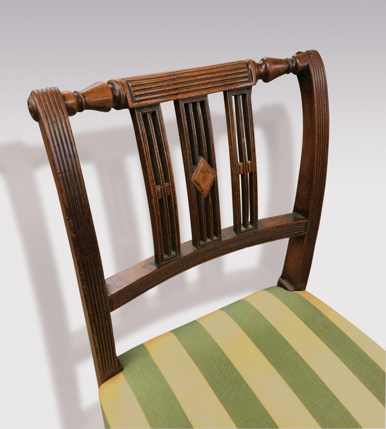 A set of six early 19th century Regency period mahogany single dining chairs, having reeded supports and turned top rails with reeded splats centred by boxwood and ebony strung diamond panel, above stuff over seats supported on ring-turned tapering