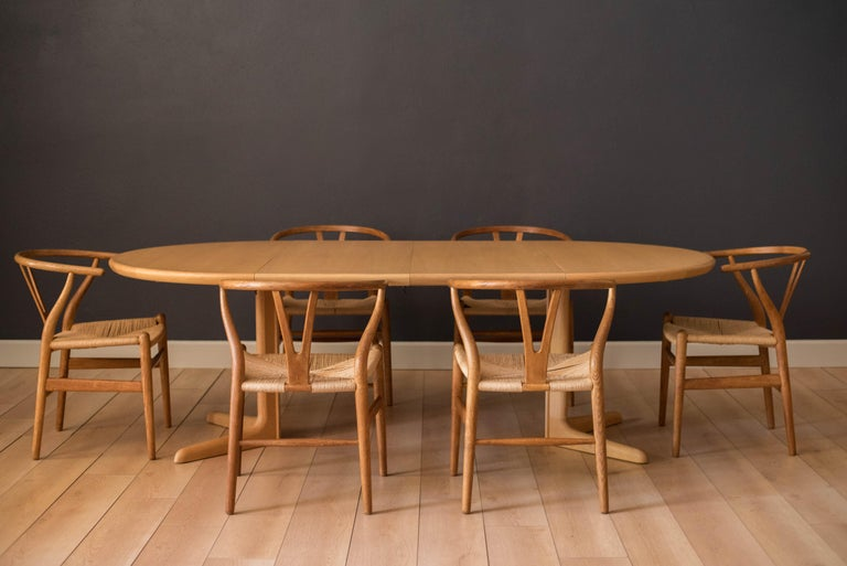 Mid-Century Modern Danish dining chairs designed by Hans J. Wegner for Carl Hansen & Søn manufactured in Odense, Denmark. This set includes six dining chairs with sculpted oak frames and handwoven paper cord seats. Backrest transitions to armrest in