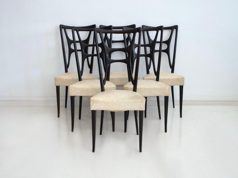 Set of six chairs made in Italy, circa 1950. Beautiful ebonized wood back and structure, upholstered seats covered in imitation leather. Some discoloration and stains on upholstery, broken corners.