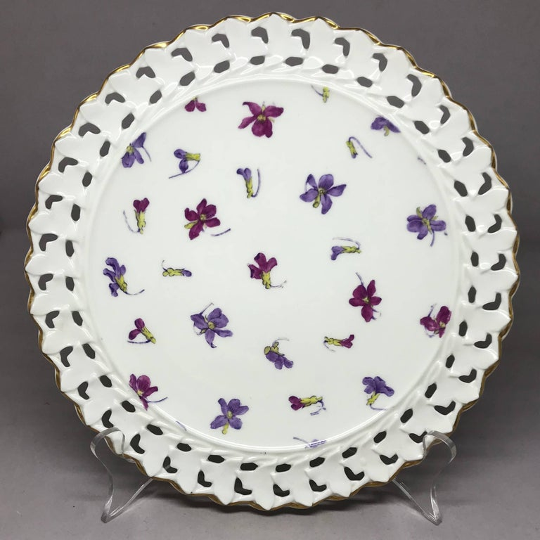 Set of six pink and purple floral gilt plates. Six white plates decorated with purple and magenta floral sprays bordered in reticulated gold rims.  Marks for Cauldon. England, early 20th century. Dimensions: 9.5