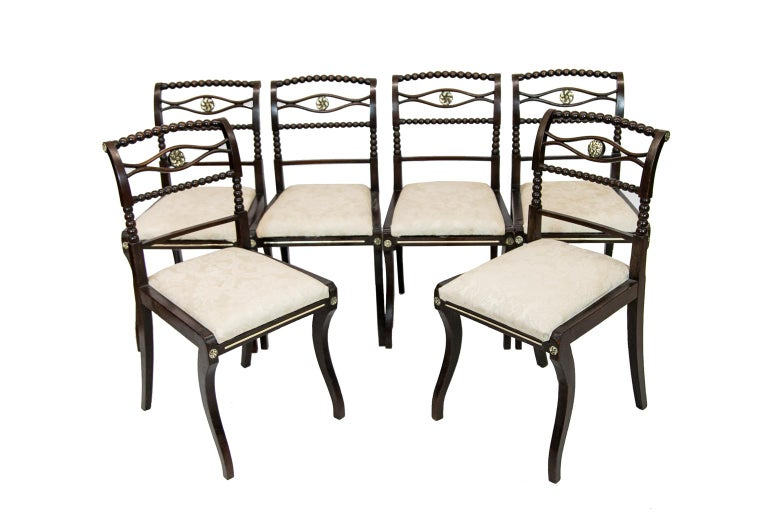 Set of six English Regency side chairs are fruitwood with floral brass medallions in the center cross splat. Each has bobbin turned crest rail, cross splat, and stiles. The front legs are ogee shaped and there are brass ray inlaid in the front