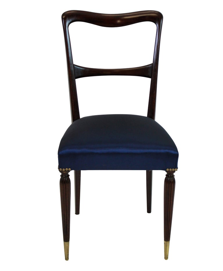 A set of six fine quality Italian midcentury dining chairs in stained beech with sculptural backs, long brass sabot feet and newly upholstered in deep blue silk.