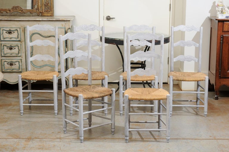 A set of six French bleached oak ladder back dining room side chairs from the 19th century, with rush seat and cylindrical legs. Born in France during the politically dynamic 19th century, each of this charming set of six dining chairs features a