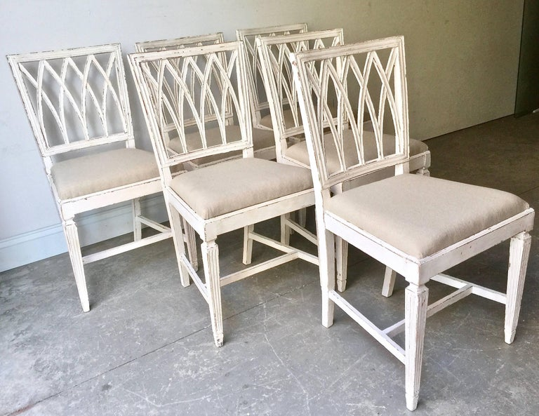 A charming set of six of French late 19th century painted side chairs with richly carved open lattice backs, loose upholstered seats in linen and fluted tapered legs with H-stretchers in time worn cream-white patina. France, 19th