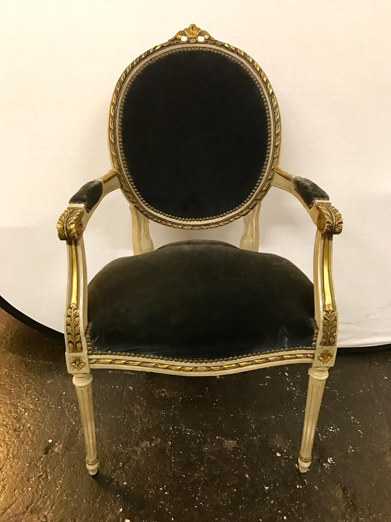 Antique cream painted French Louis XVI dining chairs with carved giltwood detail and charcoal velvet upholstery. There is one arm chair and five side chairs.