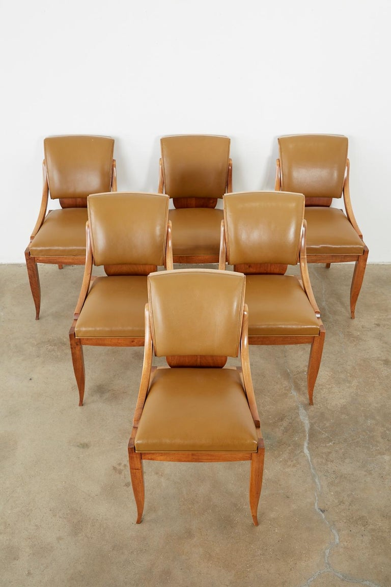 Exceptional set of French Art Deco dining chairs made in the manner and style of Rene Prou. Crafted from mahogany with gracefully curved backs and supports. Featuring a later leather upholstery of thick textured hides. The seats are supported by