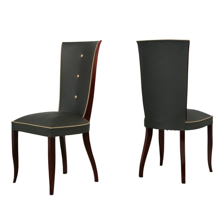 An extraordinary set of six French Art Decostyle dining chairs has been stained in a dark mahogany color and has a polished lacquer finish. The dining room chairs feature a sleek design high back, tapered legs, and are upholstered in their original