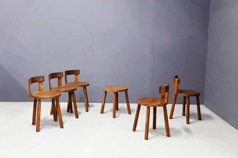 Set consisting of six chairs chairs and a French stool made entirely of wood of the 50 years. The chairs have an unusual line in fact are in the taste of Charlotte Perriand. The feet are made of cylindrical blocks of wood, while the backrest is made