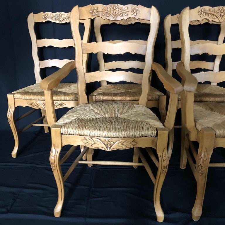 Immaculate set of six 20th century Provincial walnut chairs with lovely carving on the ladderback tops, on the apron, and on the elegant cabriole legs. Two armchairs and four side chairs. The rush seats are all in excellent condition and the chairs