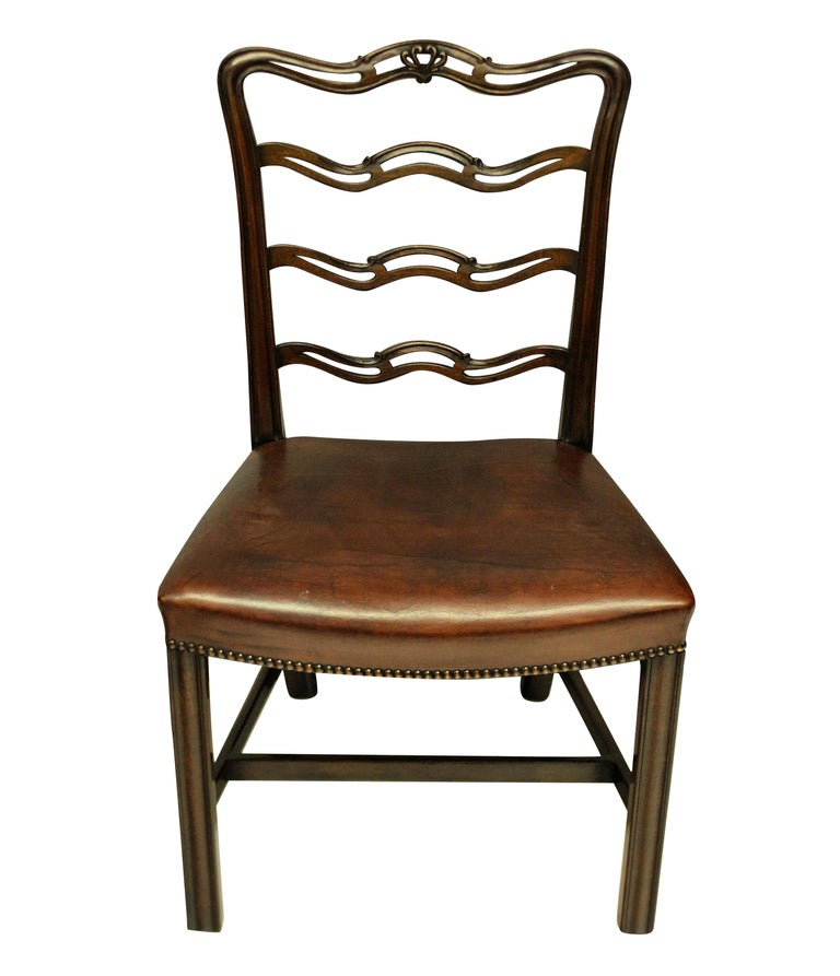 A set of six George III style mahogany ladder back dining chairs with the concave seats upholstered in leather with stud detail.