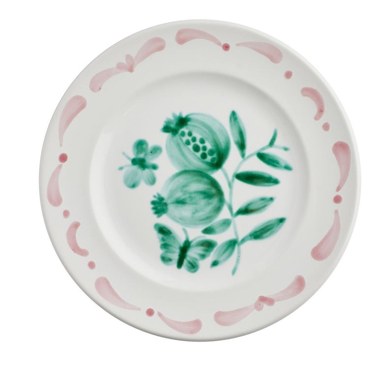 Set of six hands-free painted ceramic dinner plates. Decorated with a handpainted green pomegranate decor in the center and a hands-free painted garlande in pink. The garlande can be ordered in different colors. Produced in Austria in the typical