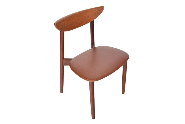 This set of six Danish modern midcentury teak dining chairs was designed by Harry Østergaard for Randers Møbelfabrik as Model 58 in 1957. Bent teak backrests feature a folded lip along the back. A cross- formed leg base supports a patinated leather
