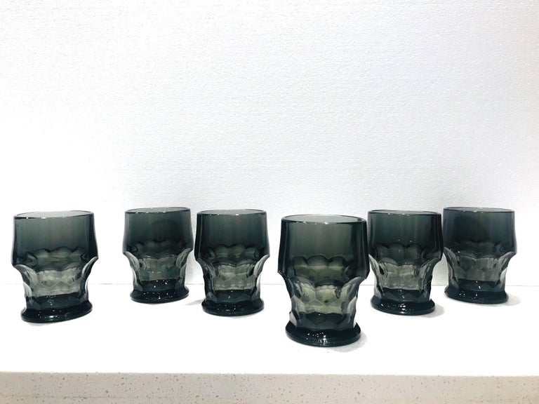 Set of Mid-Century Modern barware glasses with Gothic design. Made of translucent black glass with tapered forms and with faceted glass bases, reminiscent of scales or of stylized honeycombs. Makes a very sexy and chic addition to any barware set.