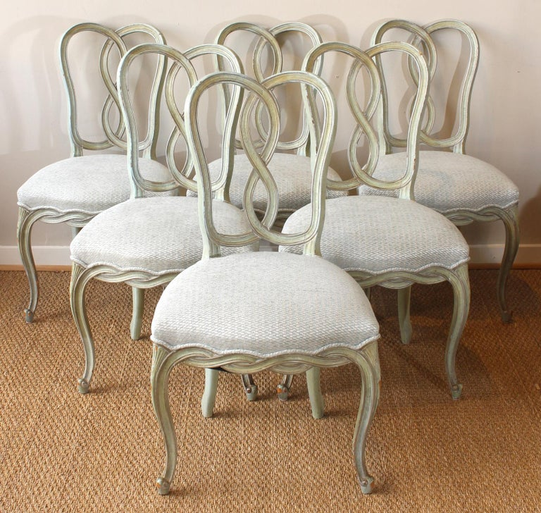 A lovely set of six mid-20th century Italian carved and painted dining chairs comprising six sides recently upholstered in a soft blue/green linen chenille fabric.