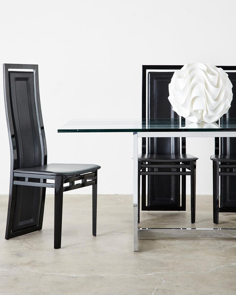 Sculptural set of six Postmodern dining chairs designed by Antonio Sibau in Manzano, Italy. Features lacquered wood frames with gracefully curved backs supporting a large leather padded back splat. The creative design allows the leather back to flex