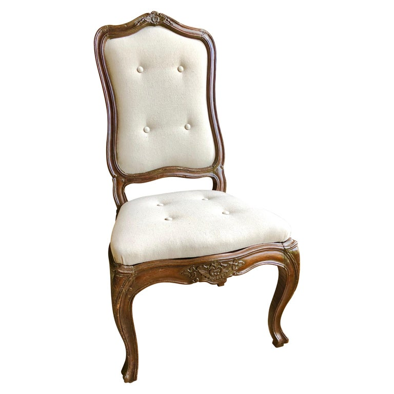 A nice set of 6 Italian dining chairs in walnut, early 19th century, in the Louis XV manner, with slip seats and backs, newly upholstered in wheat-colored cotton duck with buttons. The frames have carvings on the seat rails and top crests and are